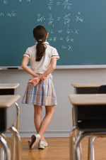 Schoolgirl Standing at Blackboard Looking at Equation